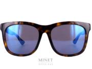 Les lunettes de soleil Gucci GG57S. Grande lunettes solaire pour homme en acétate de cellulose. La face de ces lunettes est de couleur écaille alors que les branches sont bleu et rouge. Les verres sont gris 100% uv, miroités bleus.