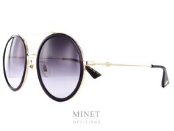 Les lunettes de soleil Gucci GG61S. Grandes lunettes rondes noir et or. La monture est en métal et les verres, dégradés gris,sont cerclé de noir.