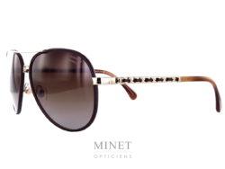 Les lunettes de soleil Chanel 4219Q sont de grandes lunettes de soleil de couleur brune et or, les verres dégradés brun 100% U.V de catégorie 3 offrent une excellente protection et vous apporteront un excellent confort aussi bien en voiture qu'à la plage. Les branches reprennent les maillons entrelacés de cuir tel la chaîne des sacs de la maison.