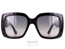 Les lunettes Gucci GG 14S. Grandes solaires rectangulaire noire de style vintage munies de large branches siglées du célèbre logo GUCCI. Les verres en polycarbonate sont dégradés gris et 100% uv.