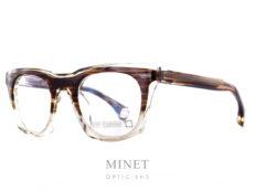 """Les Blakes Kuwahara Cody fog sont des lunettes optique pour hommes de forme carré ayant la face et les branches épaisses. La monture est de couleur cristal avec une """"incrustation"""" de couleur imitation bois dans la partie supérieure . La matière exceptionnelle allie les couleurs écailles et transparente de façon a diminuer le côté massif. Ce qui nous donnes une lunettes très épaisse mais facilement portable et esthétiquement très légère malgré tout. Pour Blake Kuwahara, la combinaison parfaite de l'expérimentation et d'une innovation audacieuse en fait un succès immédiat. _"""