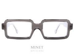Monture optique unisexe. Cette Henau Quadrum est très originale de par sa forme rectangulaire très droite et aussi grâce à ses couleurs lignée noire et blanche.