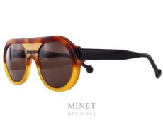 Les Henau Doga sont de très belles lunettes de soleil de couleur écaille demi-blonde combinée avec de l'écaille miel. Les branches noires donnent un joli contraste à l'ensemble. Les deuxverres brun 100% U.V. de forme ronde sont relié par un faux double-pont comblé par de l'acétate de cellulose transparent.