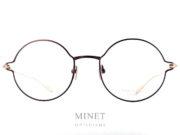 Masunaga Futura. Lunettes rondes en titane. La face est brune et les branches sont dorées. Le titane japonais nous donnes une garantie de légèreté et de solidité. De plus, il est hypoallergénique. Créée en 1905, la marque Masunaga est l'un des fleurons de la lunetterie japonaise. Ces modèles fabriqués avec rigueur et précision – elles passent par plus de 200 étapes manuelles – ont un style plutôt rétro. On retrouve beaucoup de lunettes Pantos ou rondes en acétate et en métal. Les collections de lunettes de soleil rétro et de vue restent classiques mais sont toujours de très belle facture. La marque a reçu une pluie de récompenses ces dernières années avec notamment deux Silmo d'Or. En 2014, la lunette de soleil « Campanule » en collaboration avec le styliste Kenzo Takada remporte un très grand succès. En 2015, c'est la lunette optique « GMS 106 » qui tire son épingle du jeu ! Masunaga ne finit pas de surprendre c'est certain!