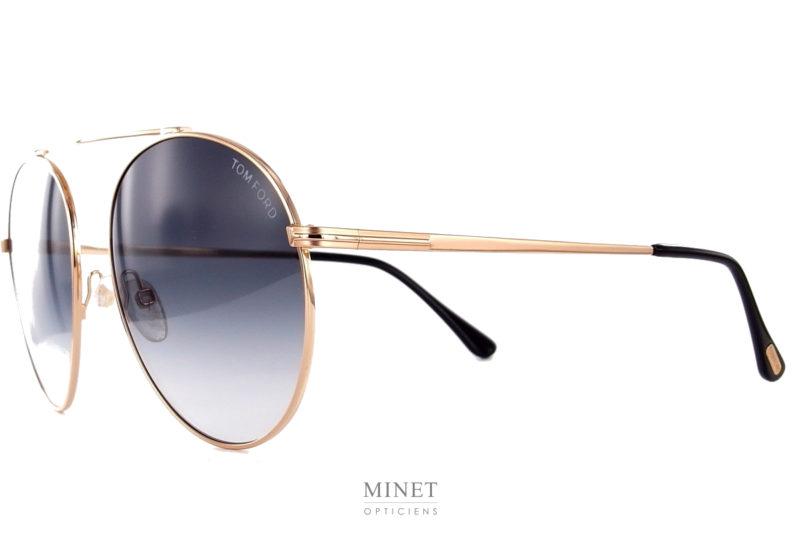 Tom Ford Simone TF571. Grandes lunettes solaires en métal doré. De formes rondes légèrement tombantes, elles rappellent la forme des pilotes mais sans le double pont. Ici, l'originalité, vient du faite qu'on a gardé que le pont du haut.